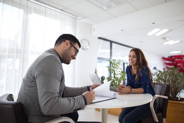 homem assina contrato trabalho em mesa com mulher