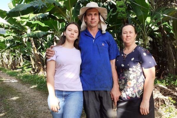 filha com pai e mãe em plantação bananas