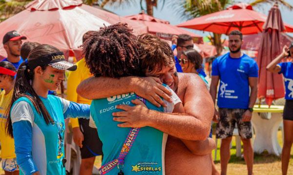 homens se abraçam em praia