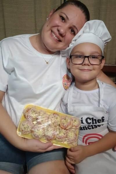 Mãe abraçada com filho vestido de chef de cozinha