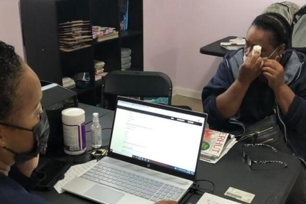 mulher chorando em mesa com notebook e outra mulher de máscara