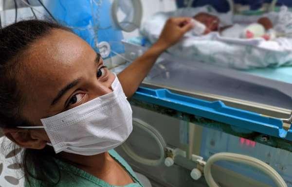 mãe segura mão filha incubadora