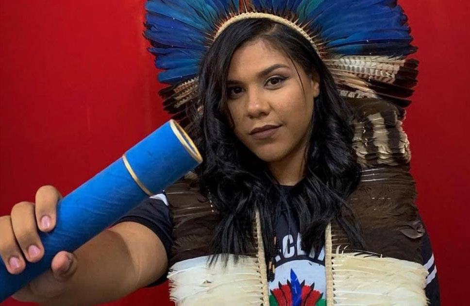 jovem indígena com cocar segurando diploma