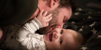 pai beija bochecha filho sorrindo