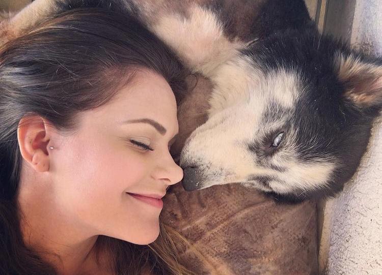 mulher deitada com cadela olhos fechados