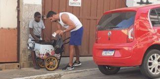Homem ajuda menino na rua com seu carrinho de picolé