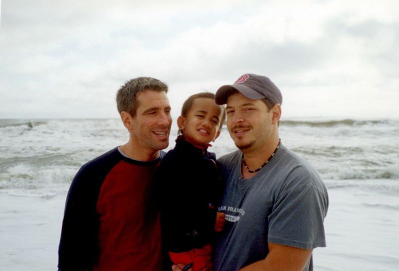 casal gay segurando filho praia