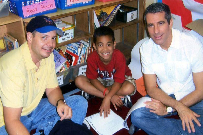 casal gay fazendo tarefa escola filho sentados chão