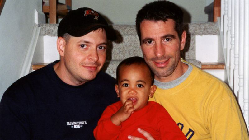 casal gay sentado escada com bebê sorrindo