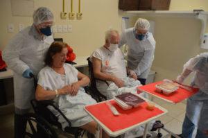 Casal de idosos almoçando com ajuda de enfermeiros