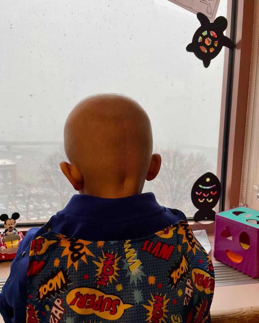 menino câncer olhando janela hospital