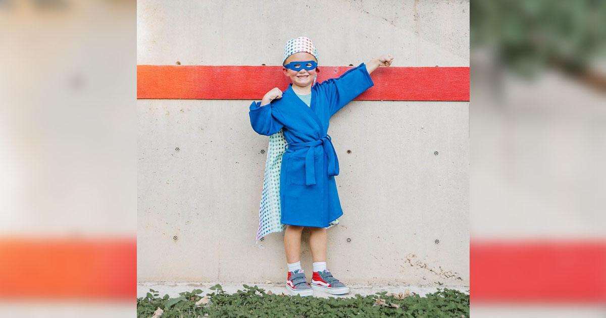 menina câncer usa roupão azul tema super-herói