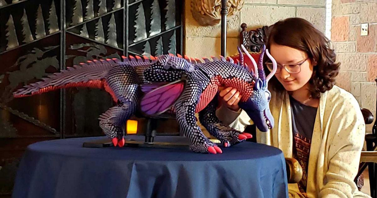 Menina acariciando robô-dragão