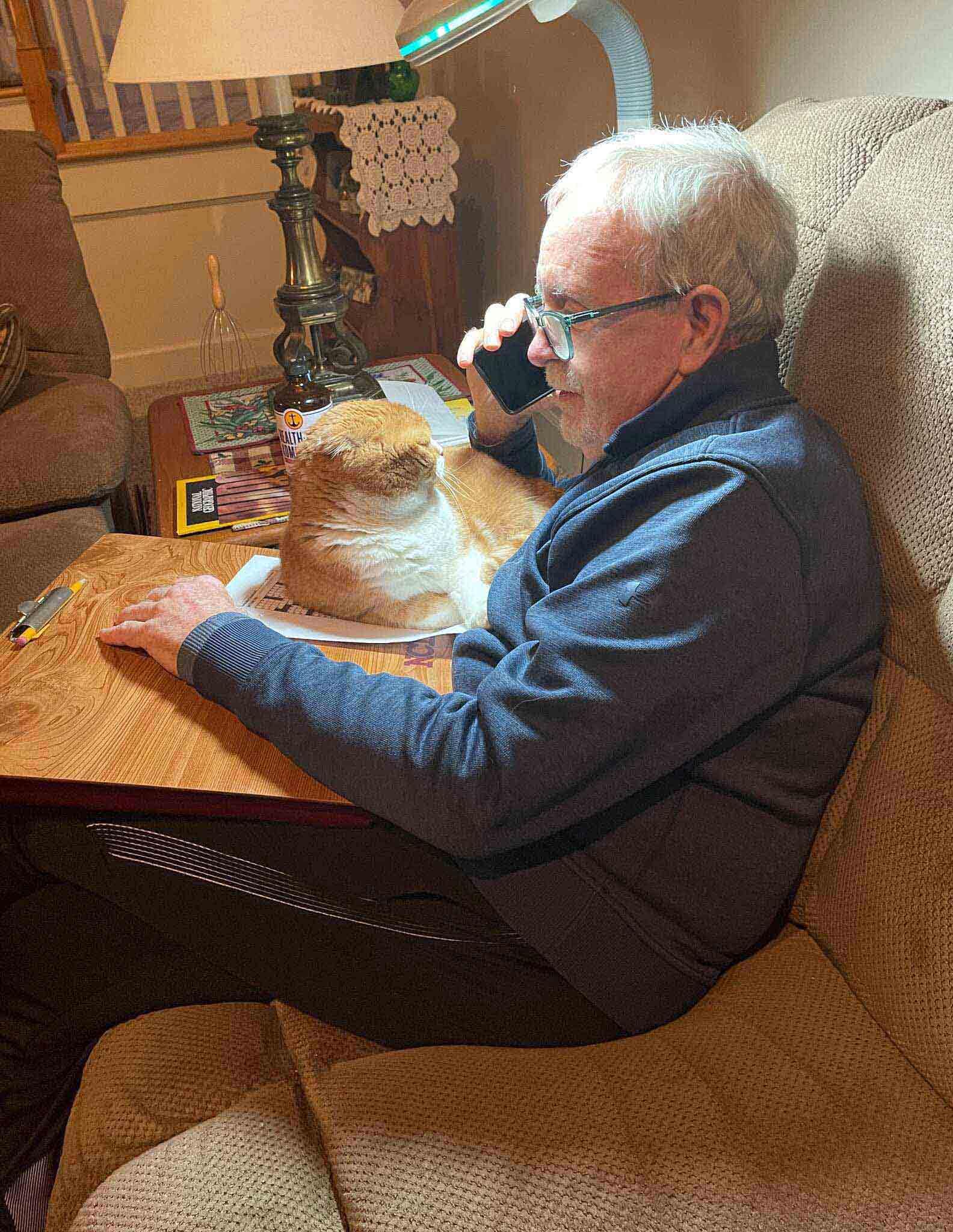 idoso falando celular gato deitado mesa apoiada seu colo