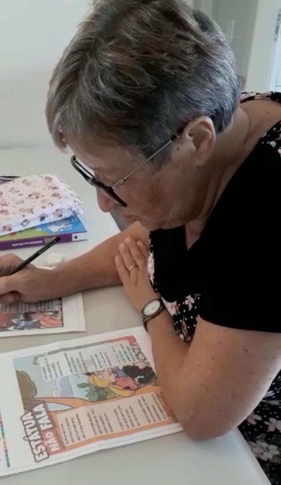 idosa estudando apostila sobre mesa