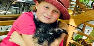 Menina abraçada com cachorro