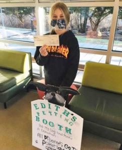 menina mostra cheque doação abrigo