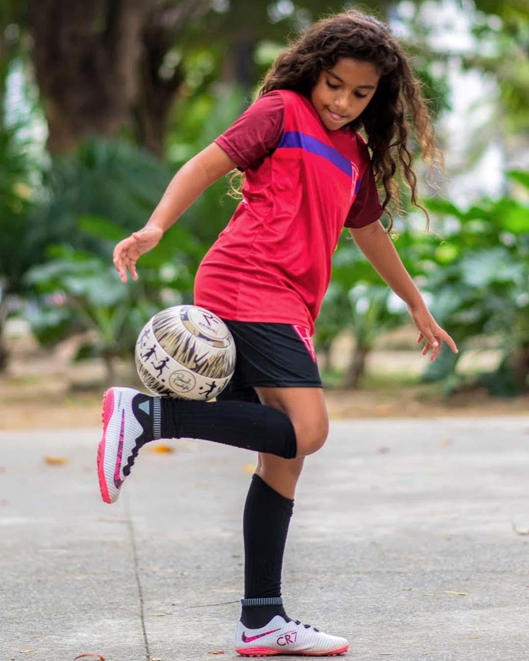 menina brincando bola futebol