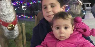 menino posa foto com irmã menor