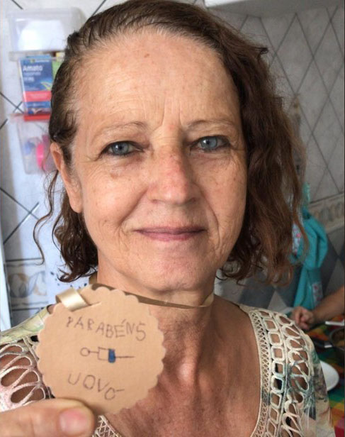 idosa segura medalha de papelão neta vacinada coronavírus