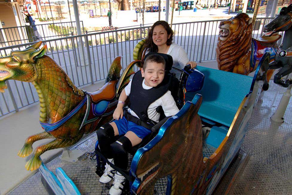 menino cadeirante brincando carrossel adaptado parque diversões