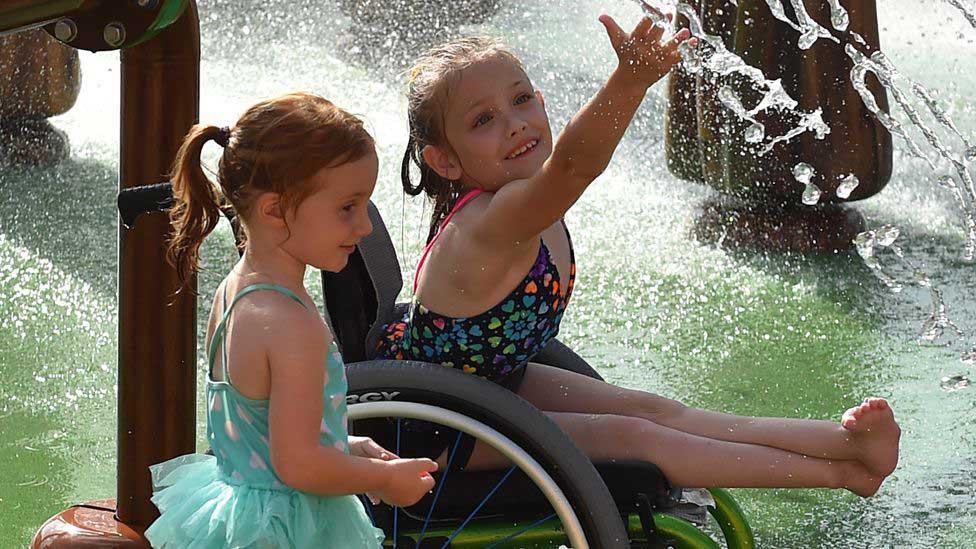 menina cadeirante diverte água parque aquático inclusivo