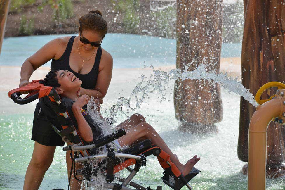 menino cadeirante diverte água mãe parque aquático
