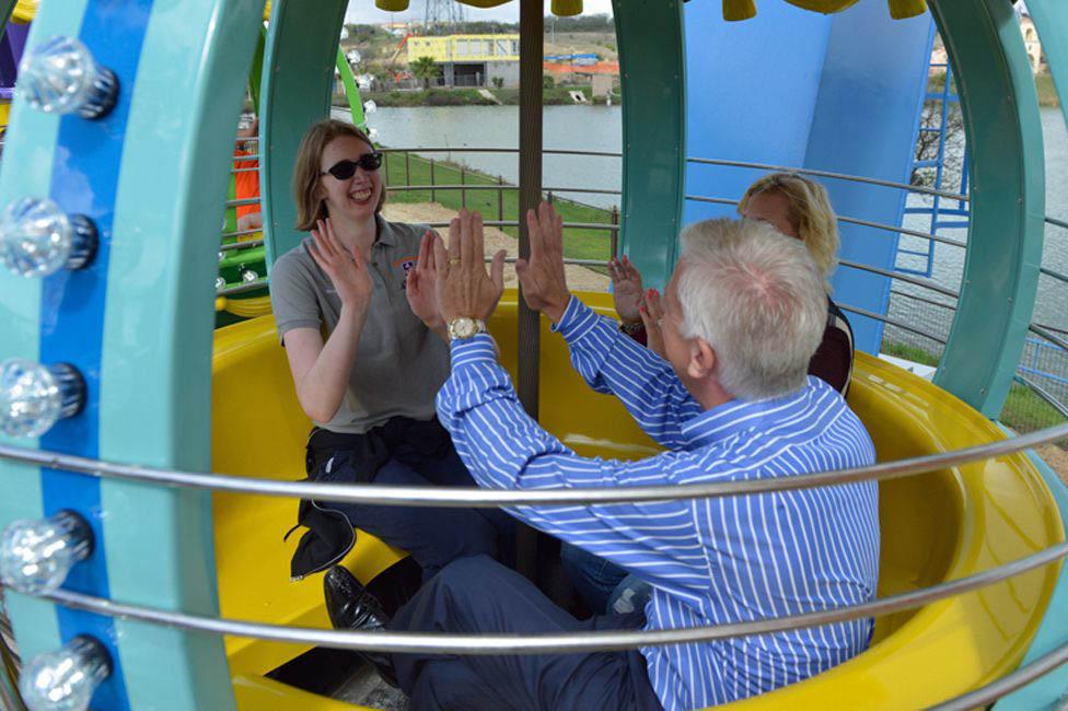 pai filha mãe roda brinquedo parque temático inclusivo