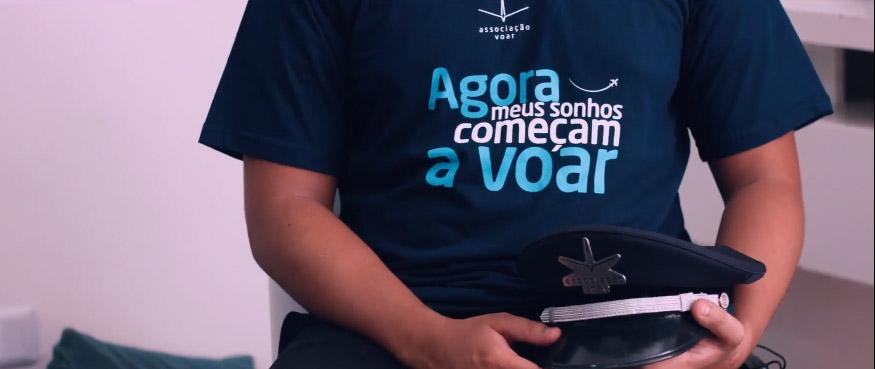 rapaz segurando chapéu piloto avião vestindo camiseta associação voar azul