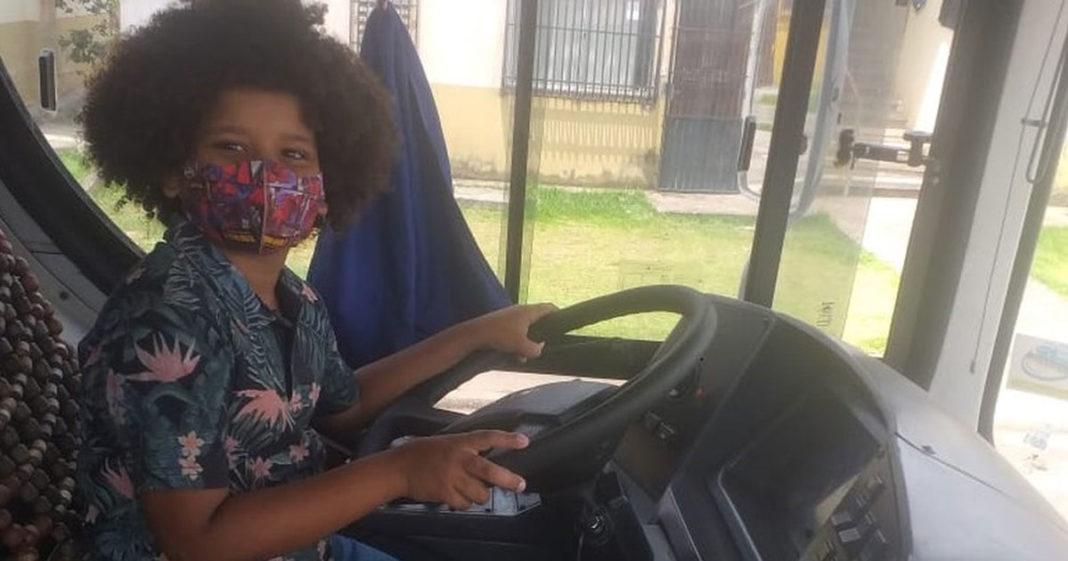 Menino fingindo que dirige ônibus