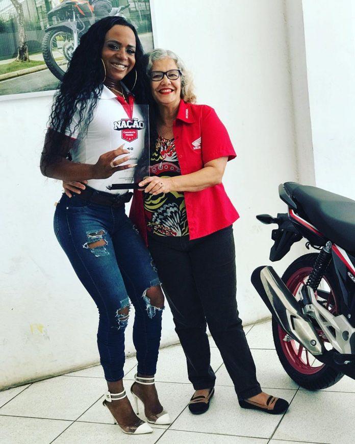 mulher trans exibe troféu melhor vendedora marca motos