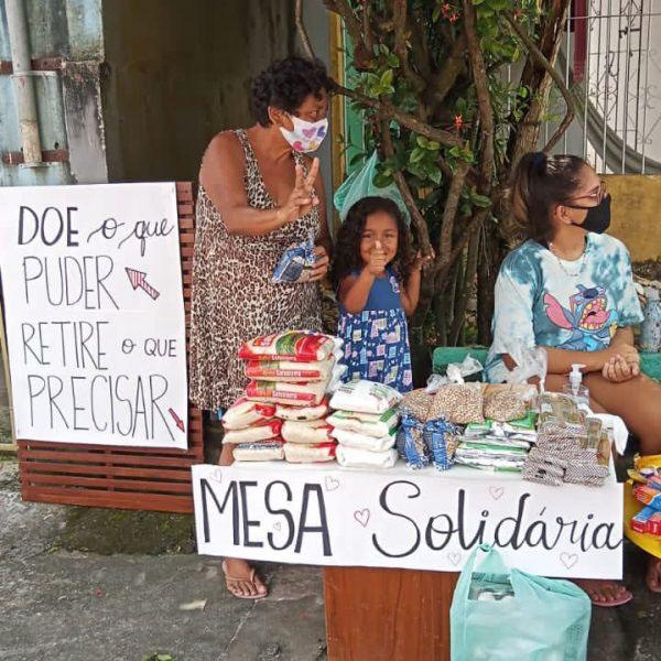 vizinhos organizam mesa solidária para doação alimentos; na foto, idosa e criança acenam