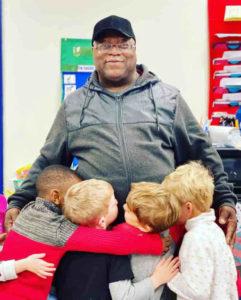 Zelador abraçado por crianças