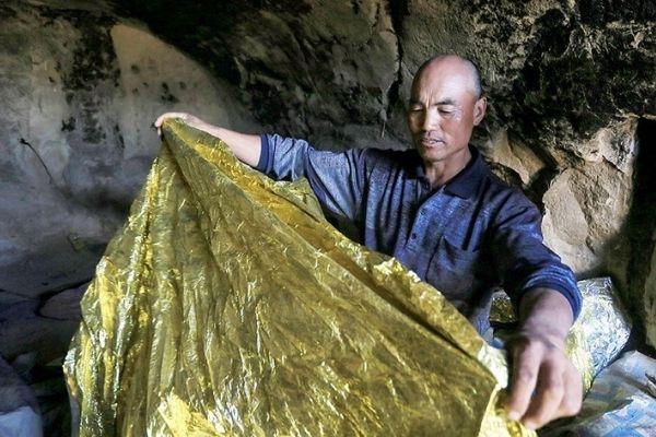 homem em caverna segurando cobertor térmico