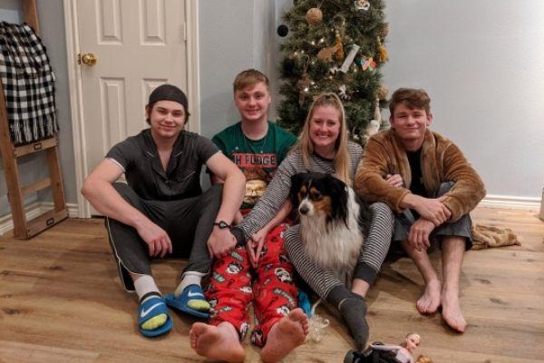 mãe com cachorro e filhos adolescentes em frente árvore Natal