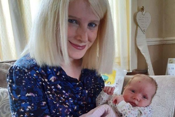 mãe com bebê recém-nascida no colo