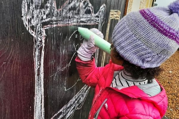 menina desenhando com giz em porta