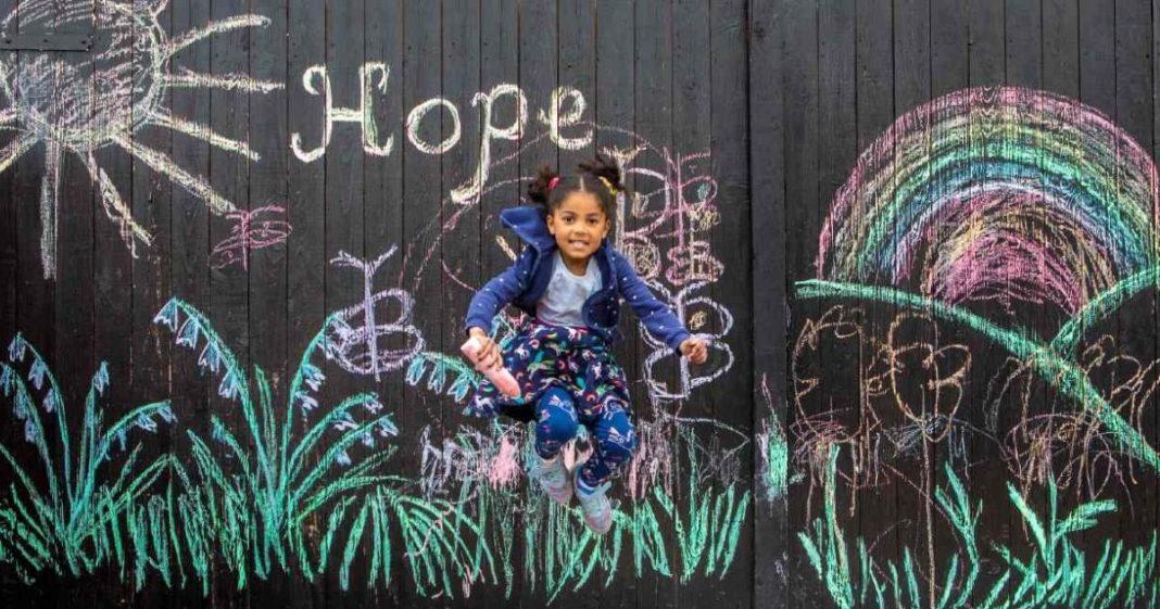 menina em frente a desenhos pintados porta garagem