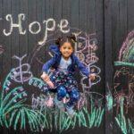 Menina de 5 anos desenha mensagens de esperança em sua garagem para alegrar vizinhos