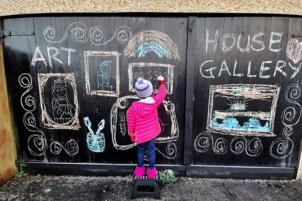 menina escrevendo e desenhando em porta