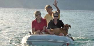 Três mulheres em barco com cachorro