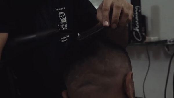 Barbeiro cortando cabelo com apenas uma mão