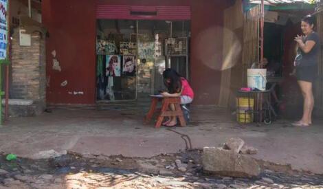 menina faz dever escola em frente salão cabeleireiro