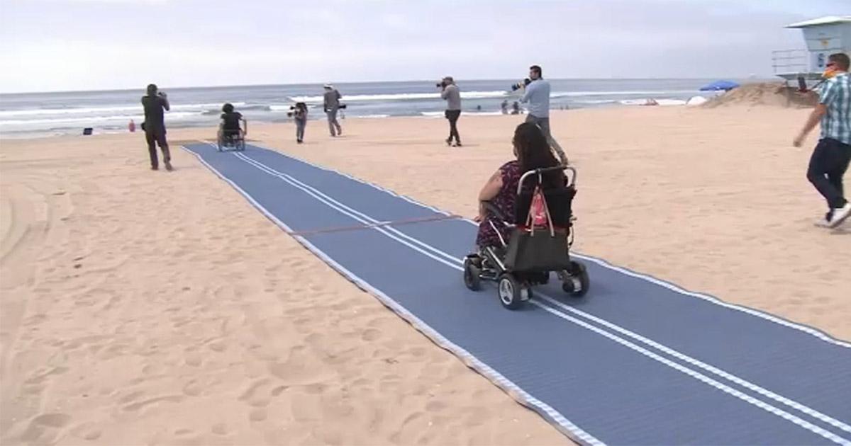 cadeirante acessa praia através tapete especial