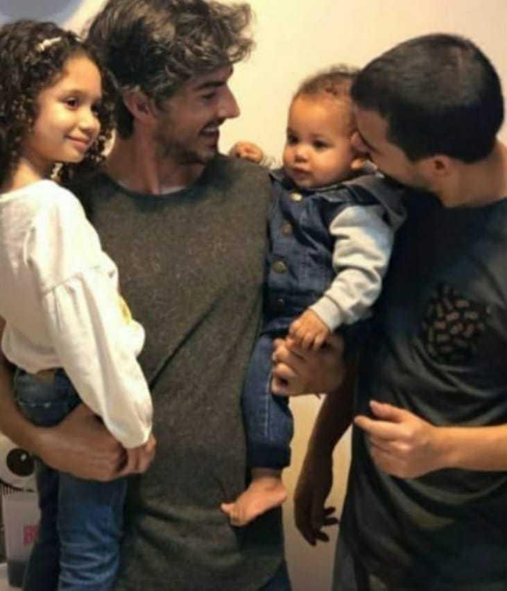 casal gay abraçando filhos adotivos