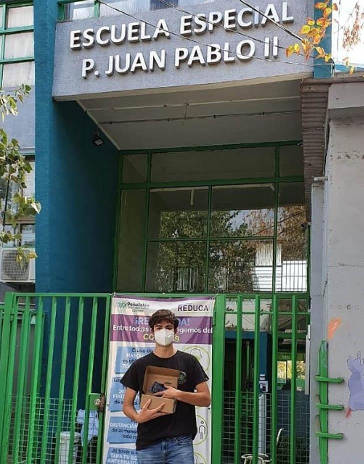 estudante frente escola caixa celulares doação