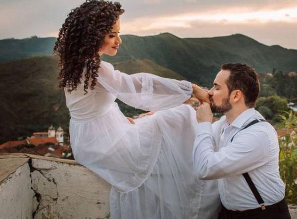 Noivo beijando mão de noiva em ensaio
