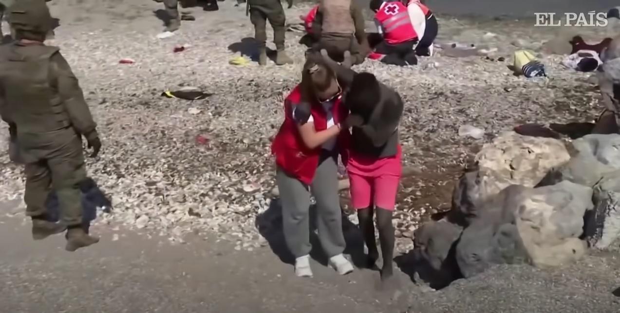 voluntária cruz vermelha abraça imigrante desesperado