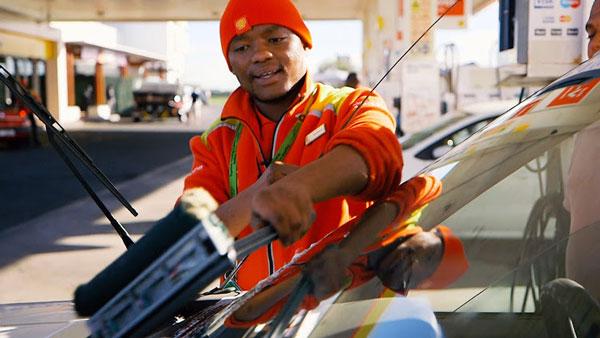 Frentista limpando vidro de carro