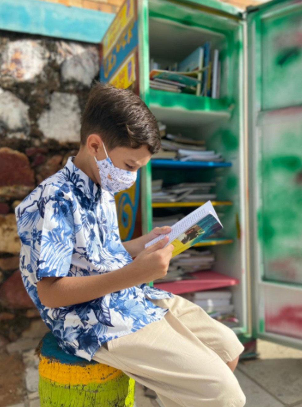 Menino lendo livros em frente a geladeira cultural